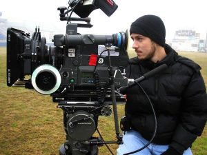young white male using a professional filming camera