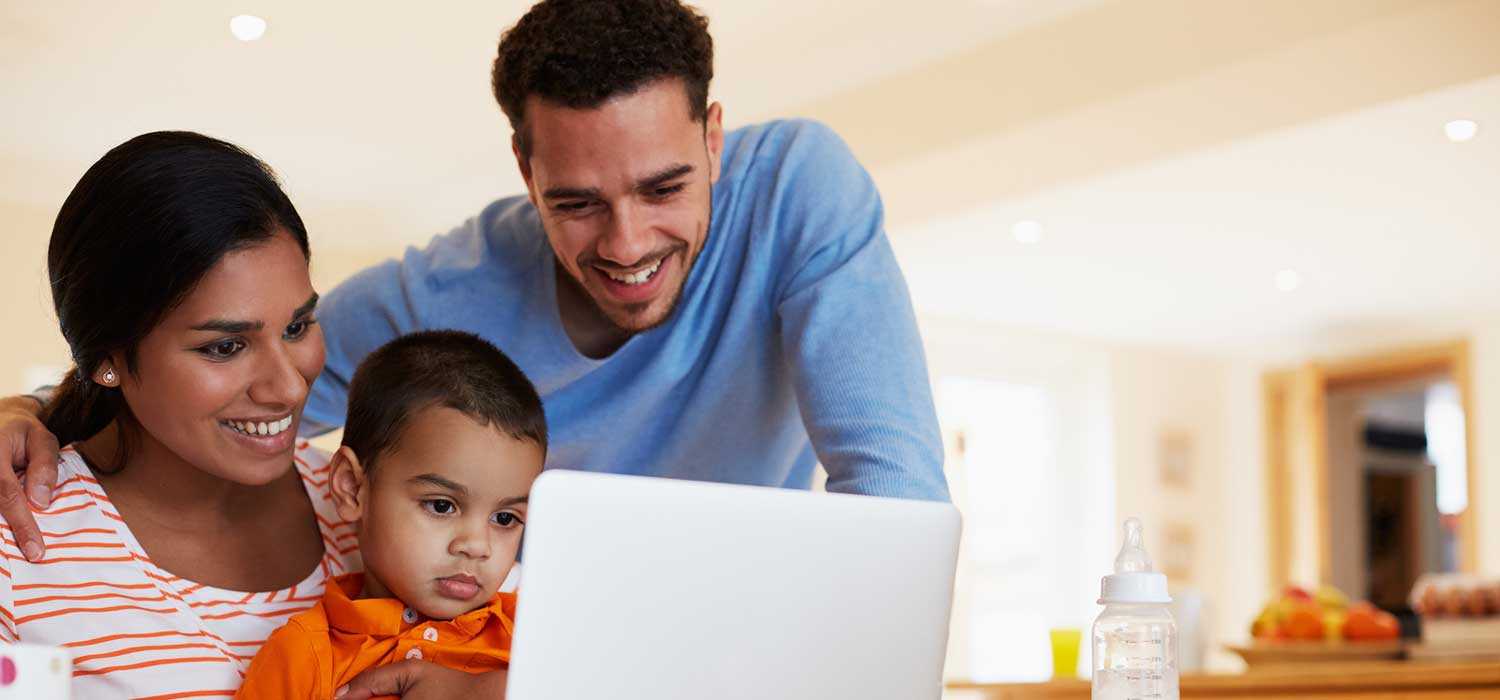 Young family with an open laptop