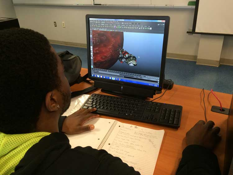 student with computer working on graphics