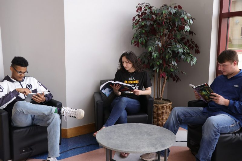 students reading sitting in chairs