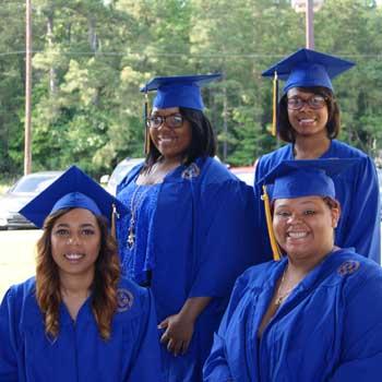 four black women in blue graduation gowns