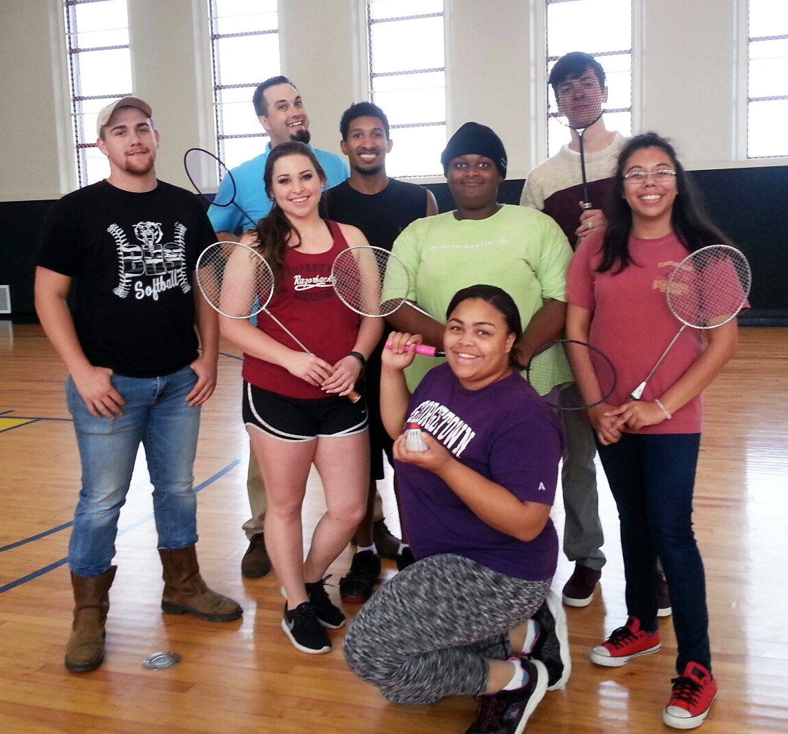 Students and employees posing after a game of badminton