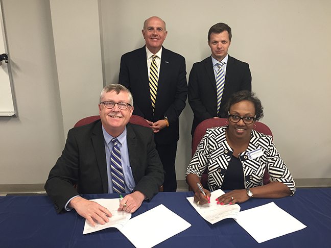 three white males and one black female at table signing papers