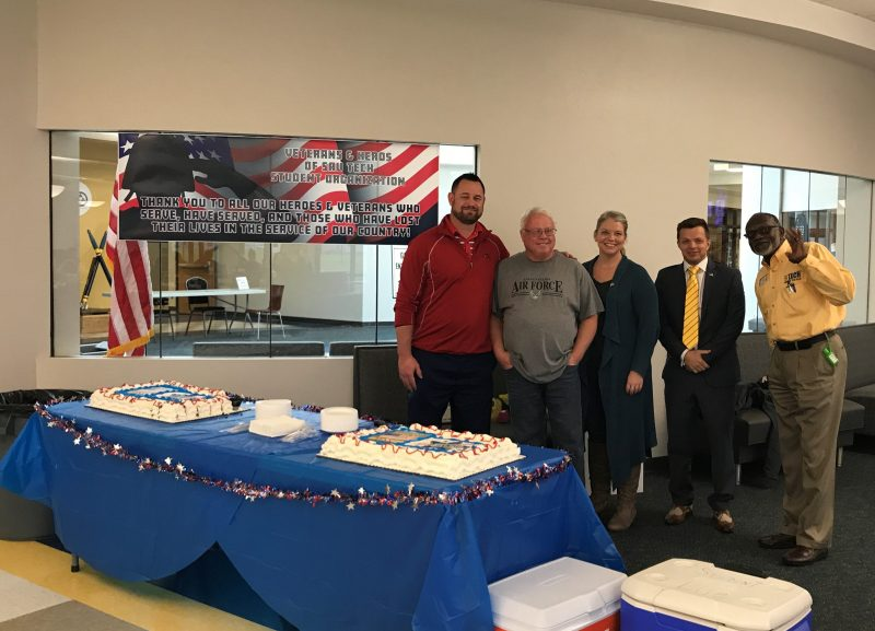 group of people with veteran banner and cake