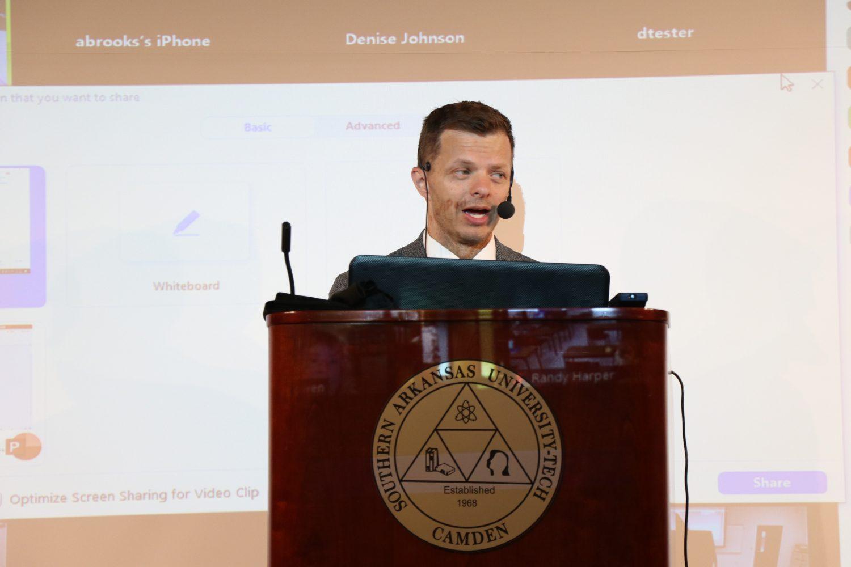 man in suit talking at podium