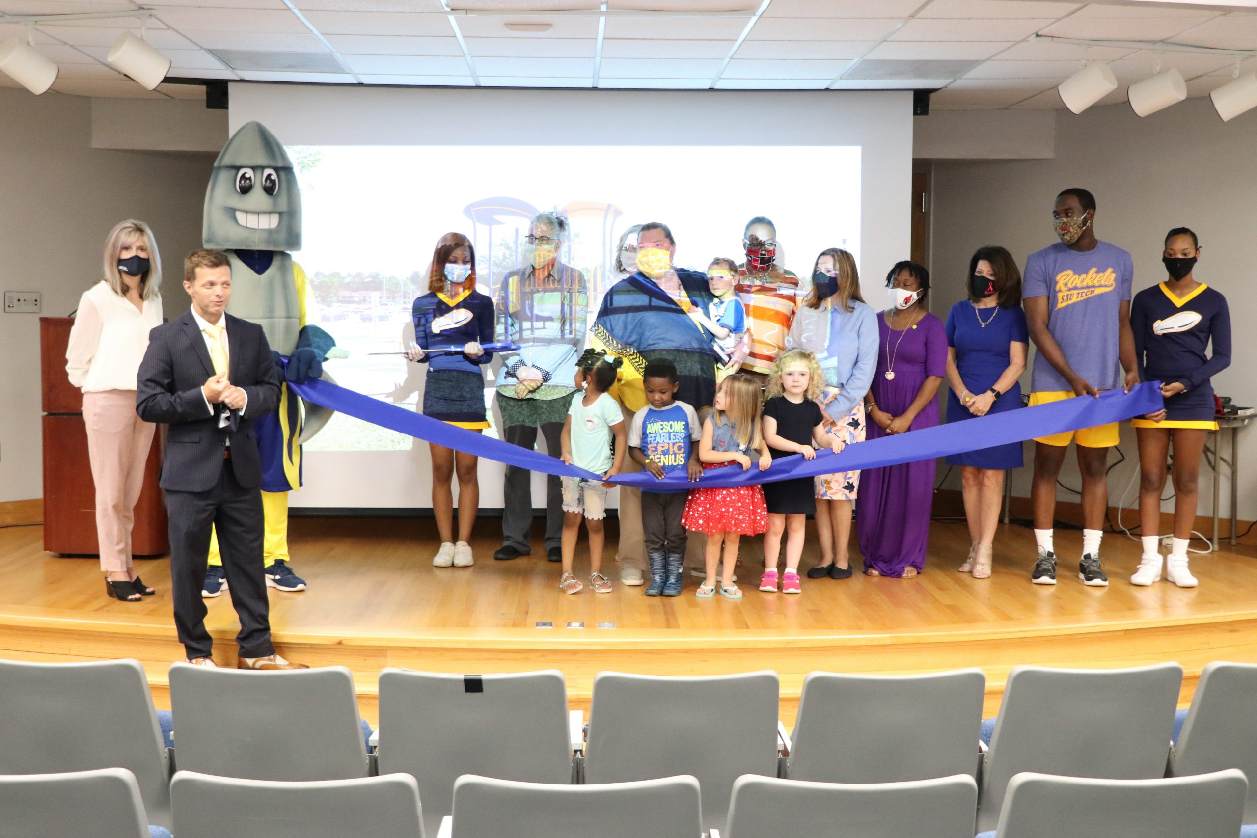 group of people and children doing a ribbon cutting