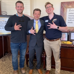 three men with hand signs