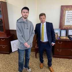 young man in gray hoodie and had and man in suit